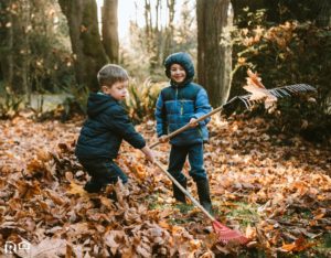 A Pair of Boys Raking Up the Autumn Leaves in Cumming