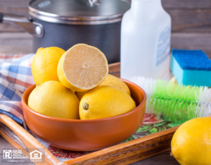 lemons in a wooden bowl with vinegar and cleaning brushes in background