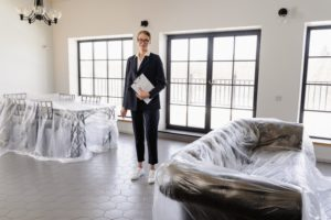 real estate agent in home with plastic on furniture