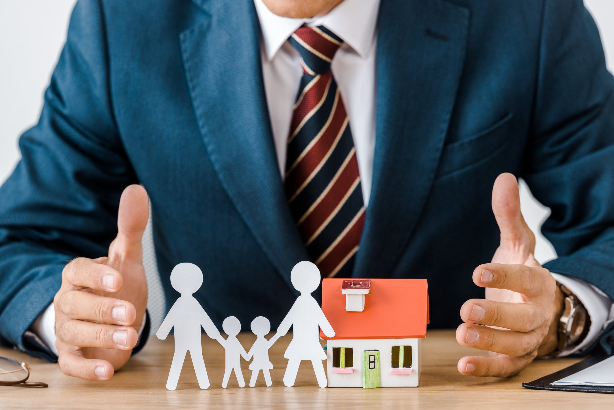 Male hands on wooden table with paper cut family and house model