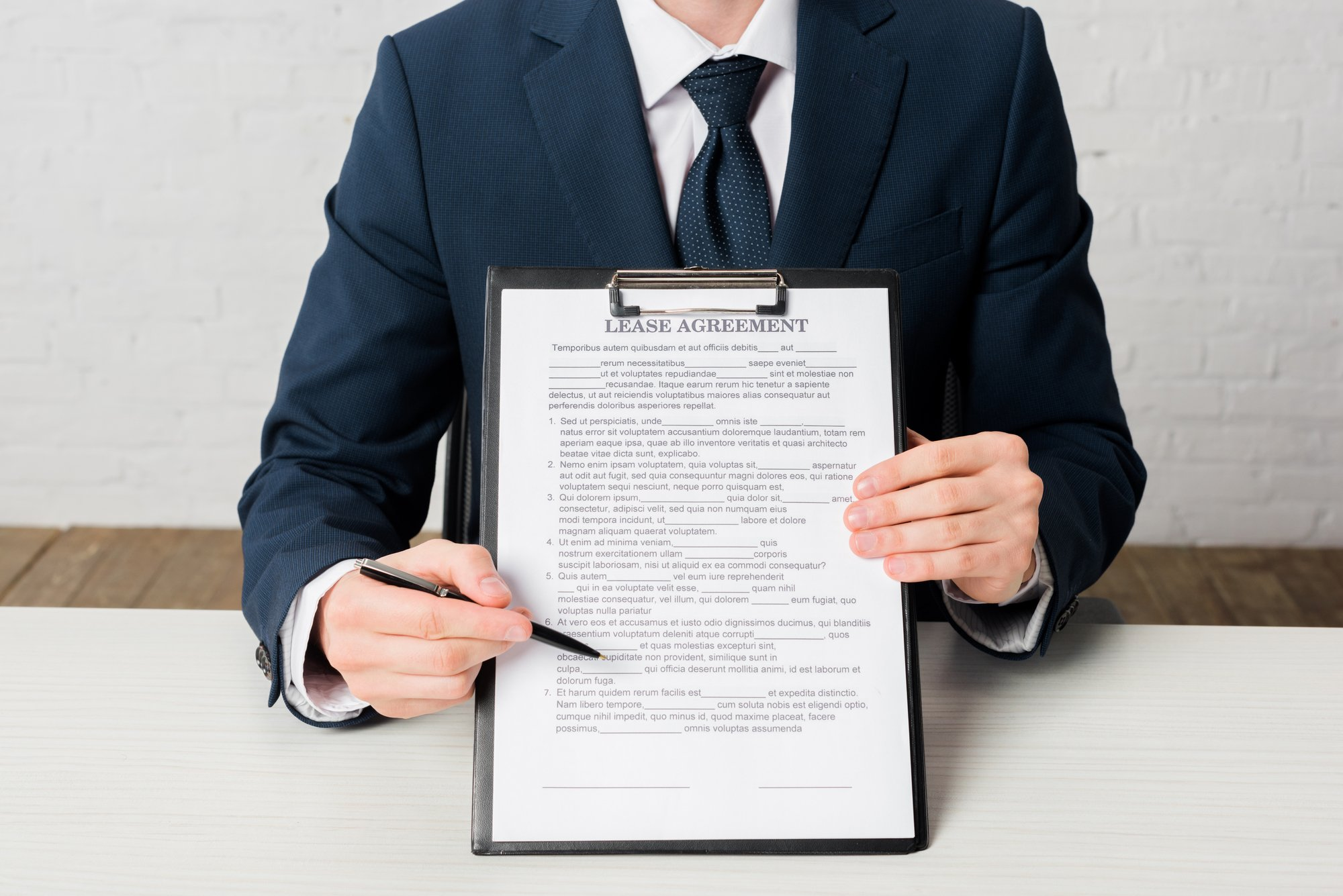 Cropped view of realtor holding clipboard with lease agreement lettering on document