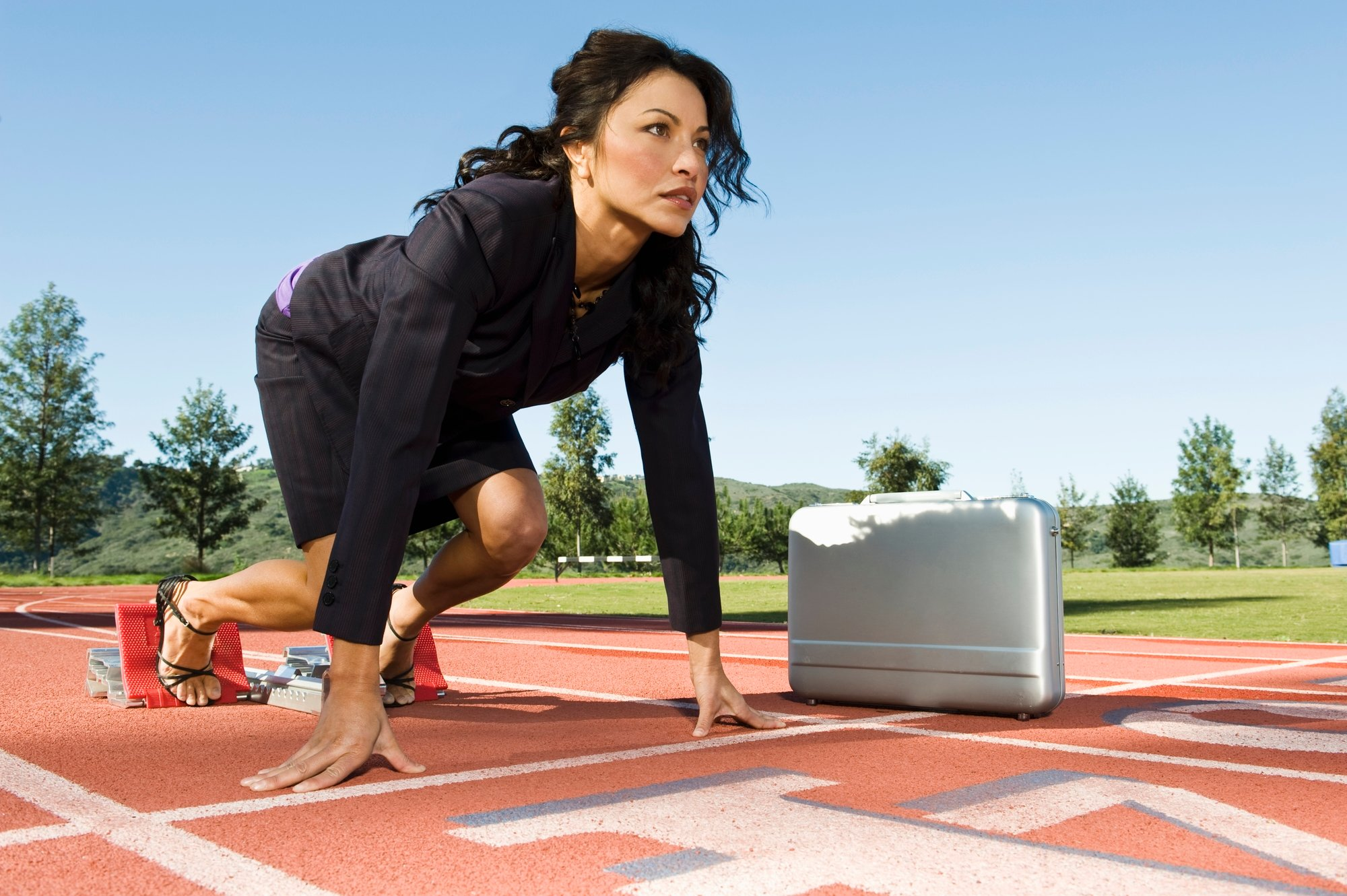 Businesswoman At The Starting Blocks With Briefcase