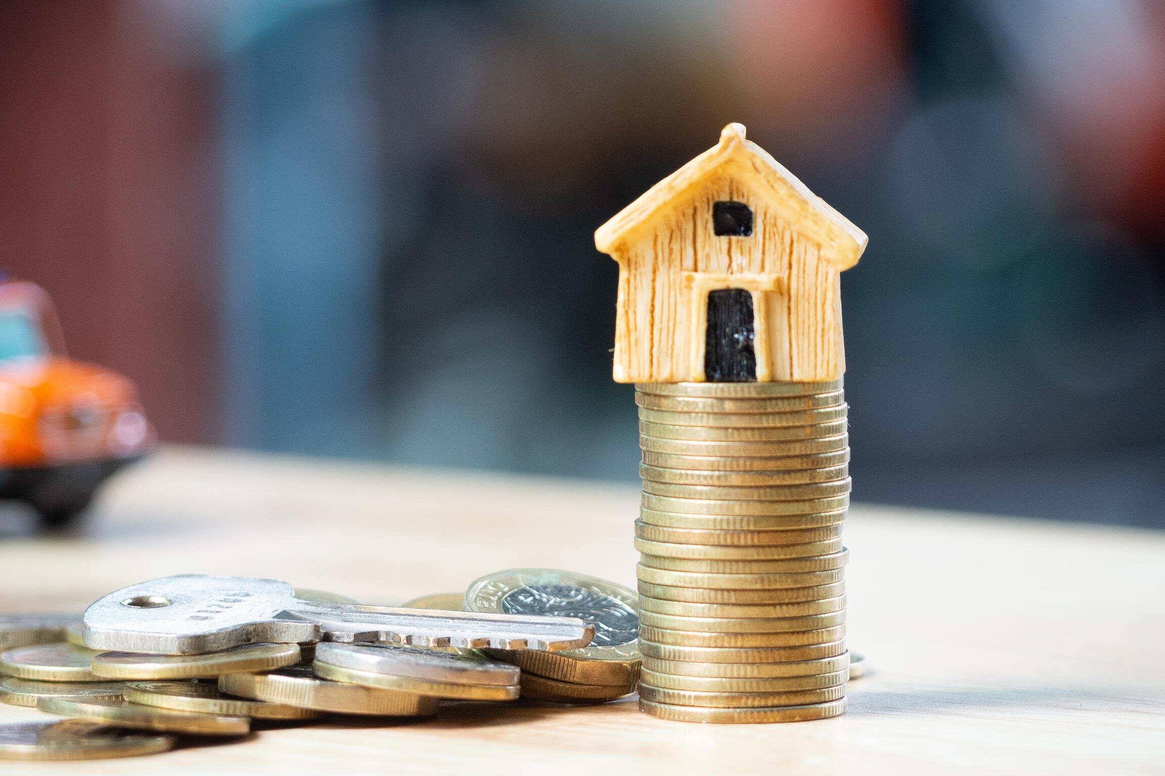 House or Home model on near of coins stack with home key. Concept for loan, property ladder, financial, mortgage, real estate investment, taxes and bonus.