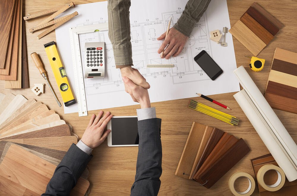 Handshake over tools and building plans