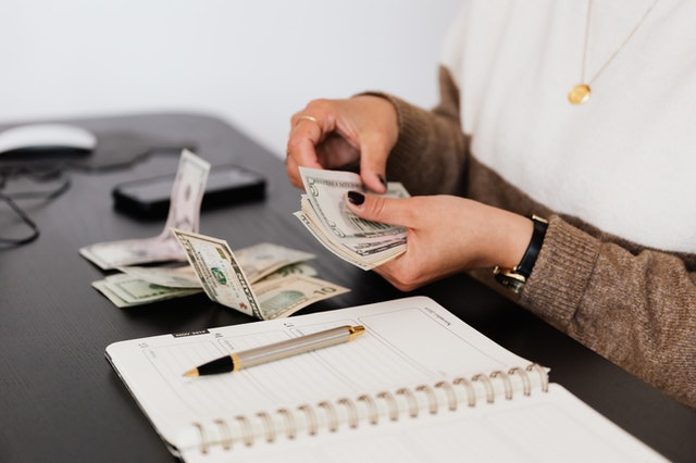 A Property Manager Counting Out Cash from a Rent Payment