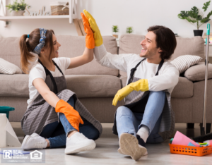 Happy Couple Giving High Five To Each Other After Spring-Cleaning