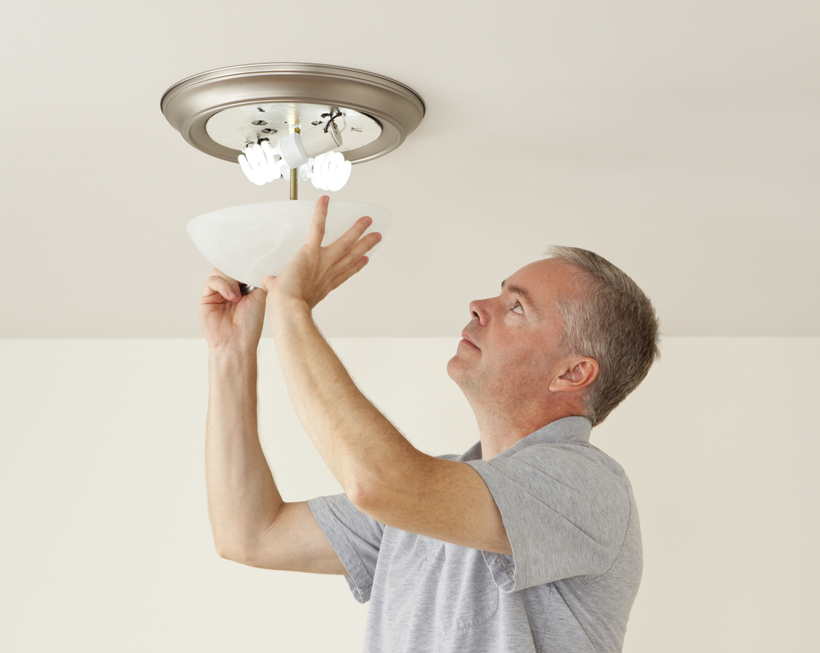 Cocoa Property Manager Placing Energy Efficient Lightbulbs in a Fixture