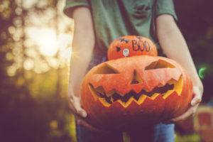 Indian Harbour Beach Resident Holding a Stack of a Decorated Pumpkin and a Jack-o-Lantern
