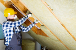 Maintenance Man Working on Insulation in the Attic of a Melbourne Beach Rental Home