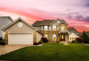 View a Beautiful Home with the Sun Setting Behind It
