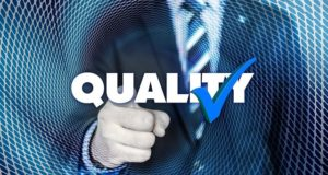 """businessman standing behind the word """"quality"""""""