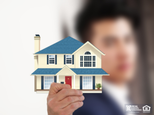 Man holding up an image of a house