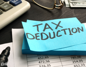 Papers Sitting on a Desk with a Sticky Note Labeled Tax Deduction