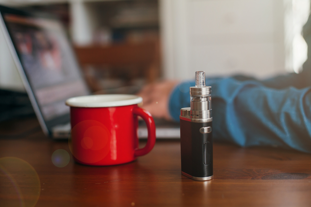 Vaping Device Standing Next to a Mug of Hot Coffee