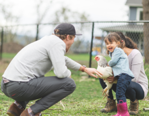 Happy Family Playing with a Chicken in the Yard of their Mobile Rental Home