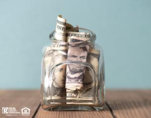 Mason Jar with Several Dollar Bills Stuffed Inside as an Emergency Fund