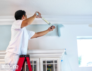 East Lyme Property Owner on Ladder Painting Interior Walls with Roller