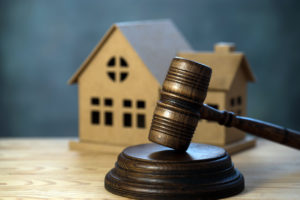 An Auction Gavel Propped Up in Front of a Replica of a House