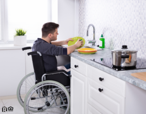 Lynbrook Cleaning Dishes in the Kitchen from His Wheelchair