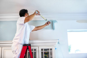 Douglaston Property Owner on Ladder Painting Interior Walls with Roller