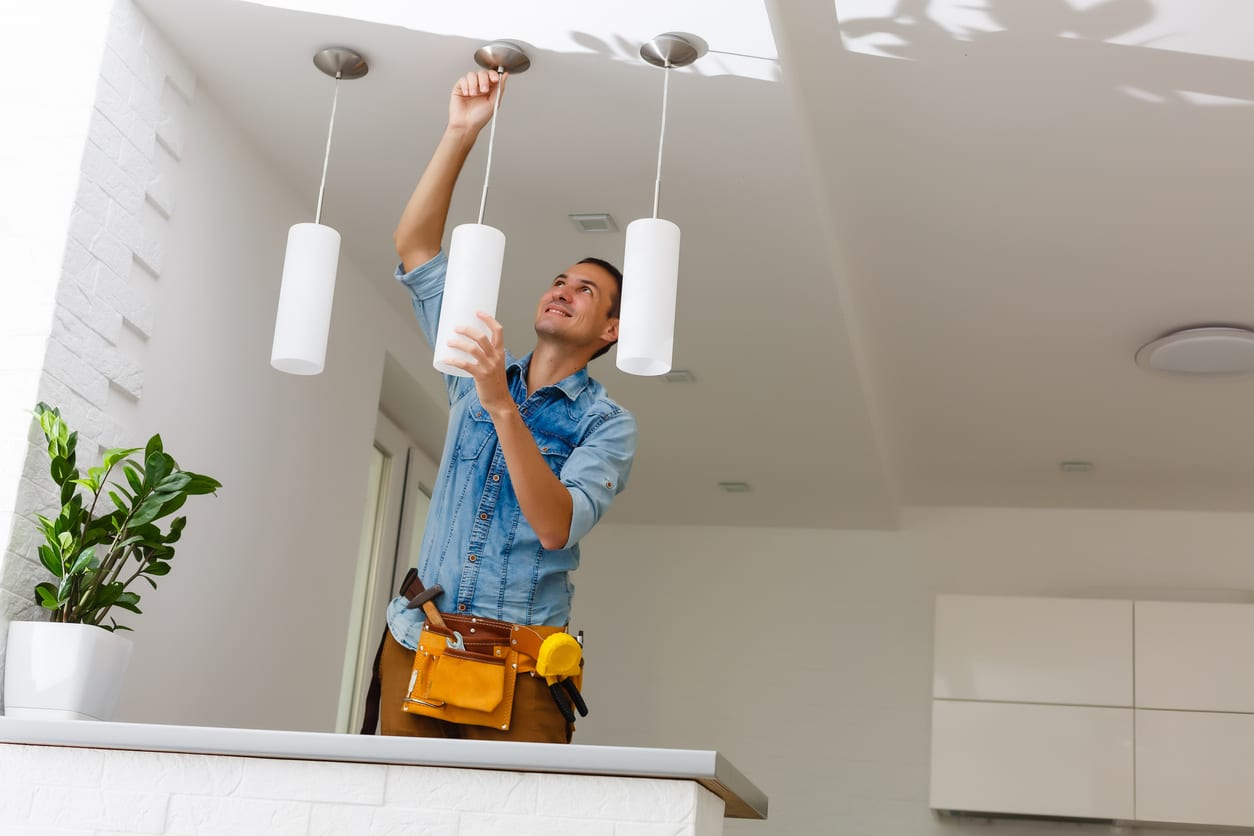 Male Electrician Fixing Ceiling Light in Kitchen