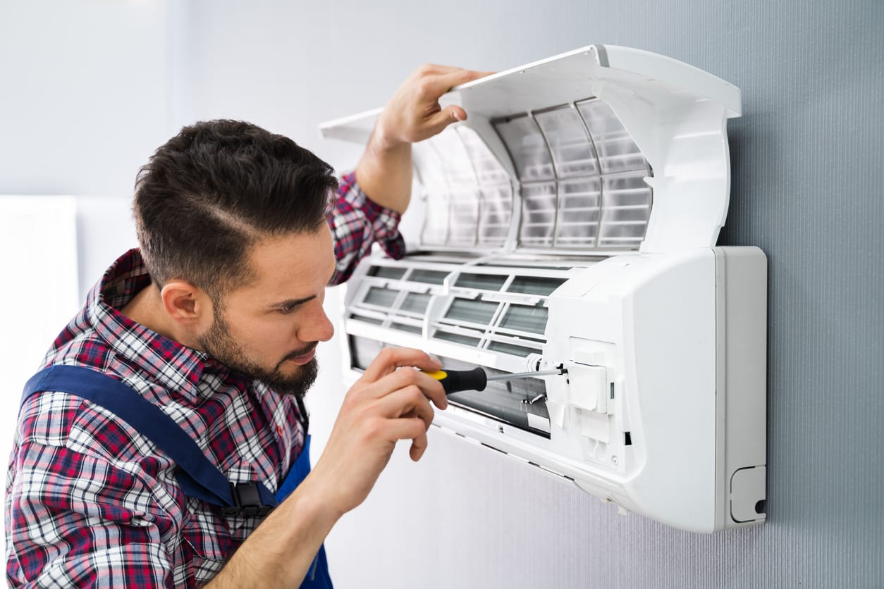 Technician Repairing Air Conditioner With Screwdriver