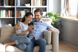 Couple in Douglaston Apartment Smiling at a Smartphone