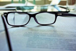 A Pair of Reading Glasses Propped on Paperwork