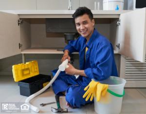 Plumber repairing clog in drain under kitchen sink