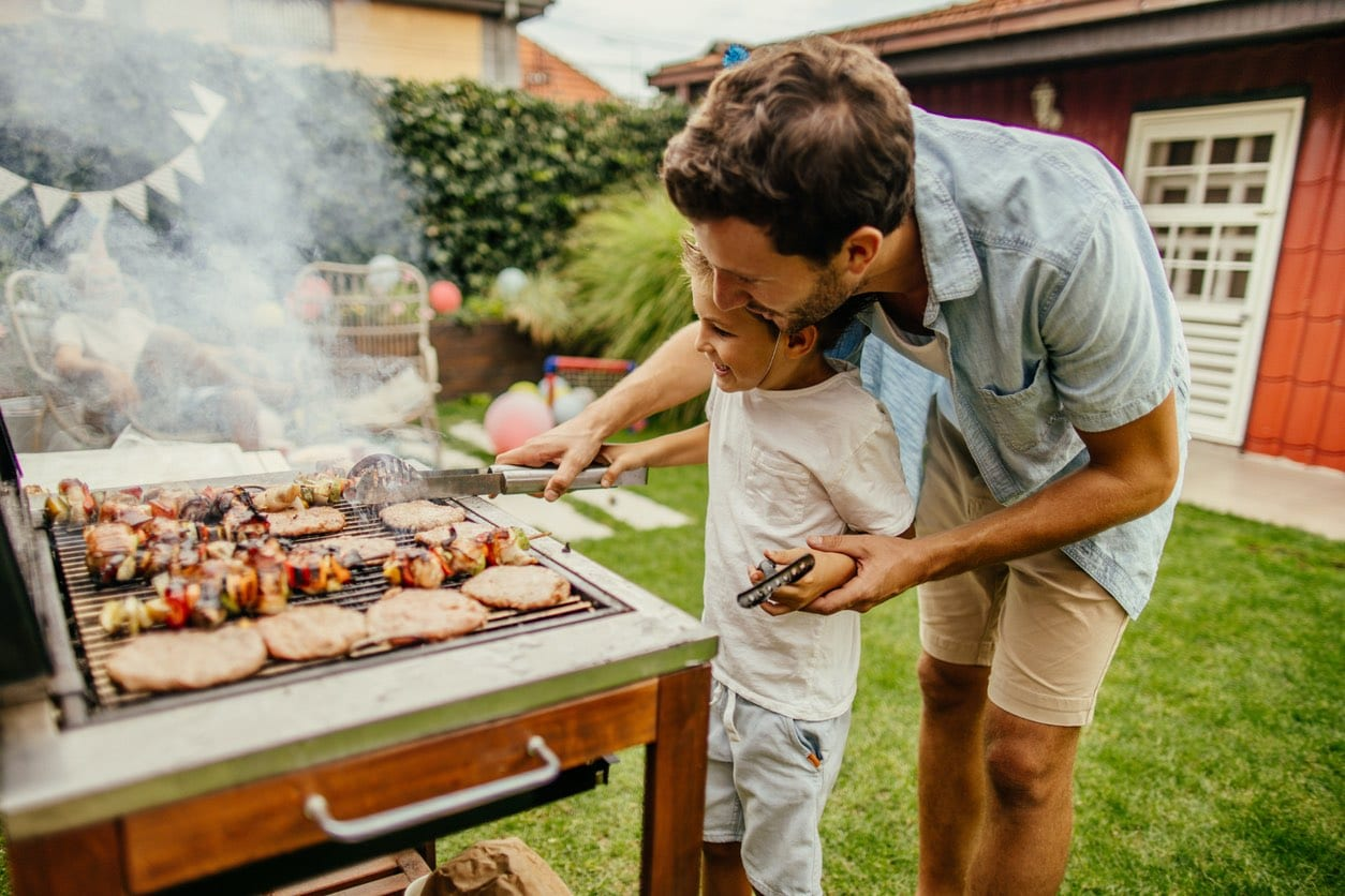 Father and Son Grilling in Yard of Lakeview Rental Property