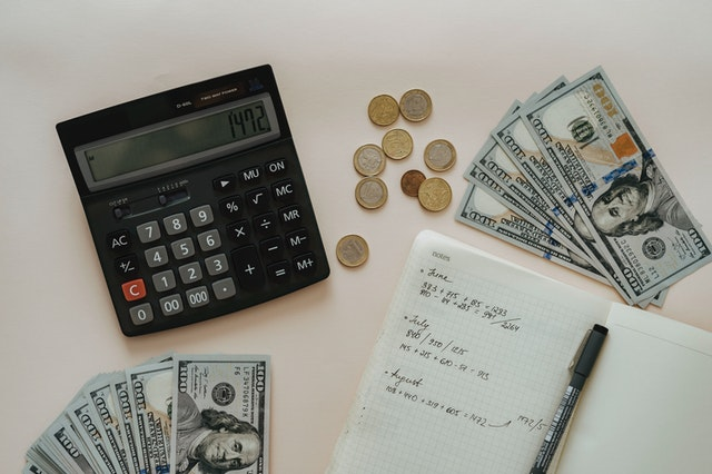 Calculator, Notebook, Coins, and Hundred Dollar Bills Displayed Across a Countertop