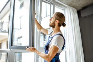 Workman in overalls installing windows in an apartment living room