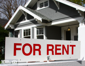 For rent sign in front of gray and white home