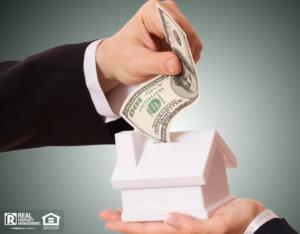 Cash Being Put into a House Piggy Bank
