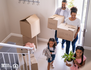 amily with two children carrying boxes and plant in new home on moving day
