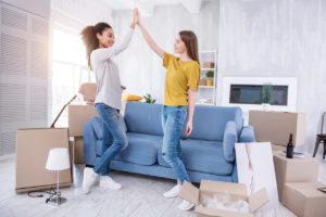 upbeat young female roommates having just successfully moved into their new flat