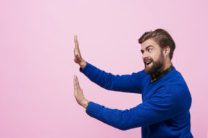 man putting hands up to distance from someone or something not shown