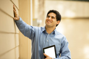 man inspects outside of building holding digital tablet