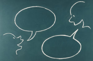 illustration on a chalkboard of two heads talking to one another