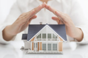 model of house with person standing behind protecting it with their hands