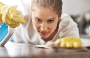 image of woman spot cleaning a table wearing gloves looking very determined to the detail of what she's doing