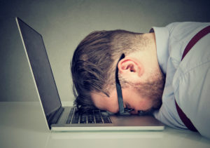 Overworked man with his face slammed down on his laptop in exhausted defeat