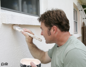 Man Painting the Exterior of a Apex Rental Property