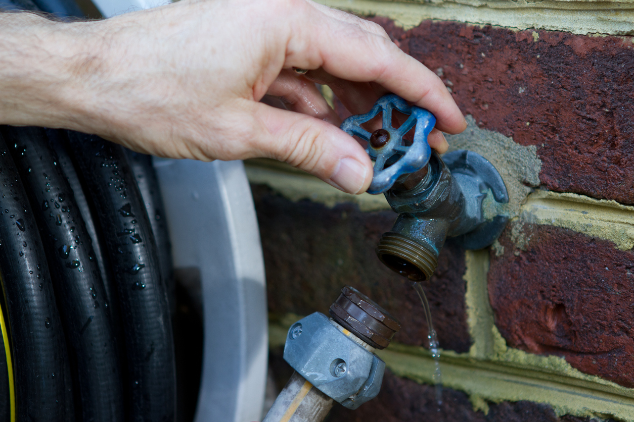 Draining water from a faucet to prevent damage from freezing temperatures.