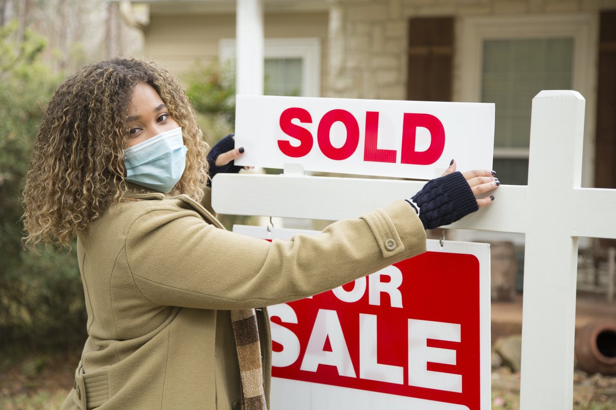 Real Estate Agent with Face Mask Holding Sold Sign