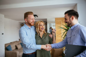 Happy Couple Closing A Great Deal on A House with Real Estate Agent