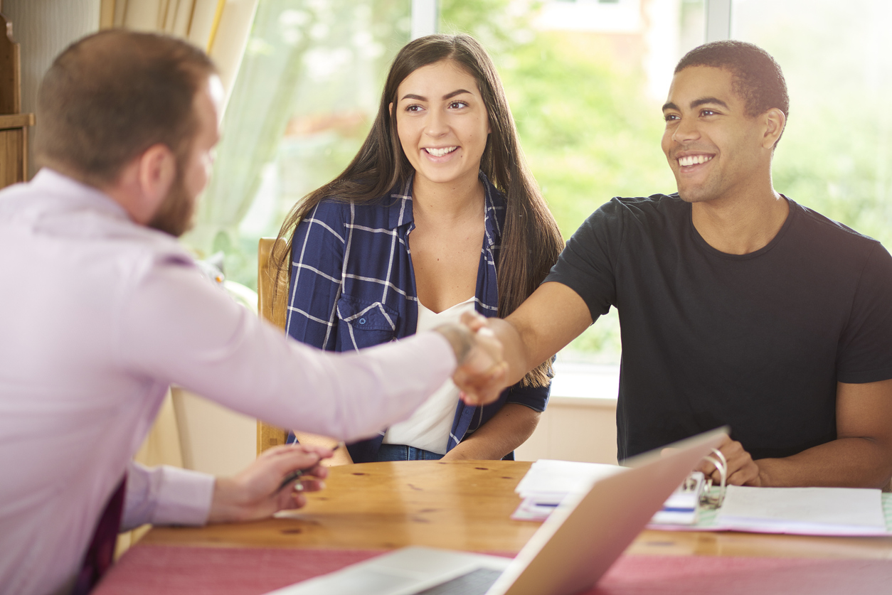 Property manager shaking hands with approved tenants for a Salt Lake City rental property