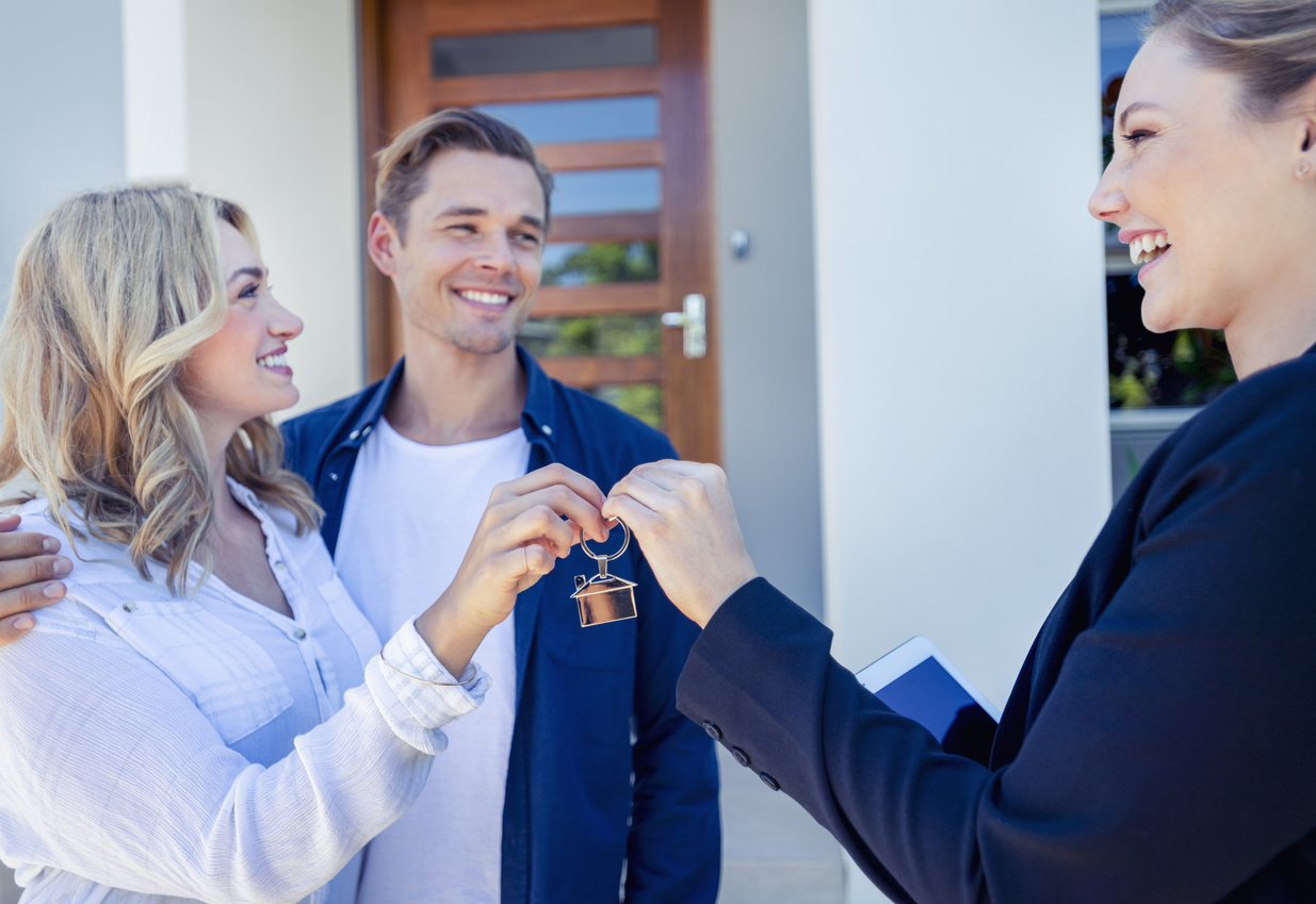 Property Manager giving young couple keys to their new rental home