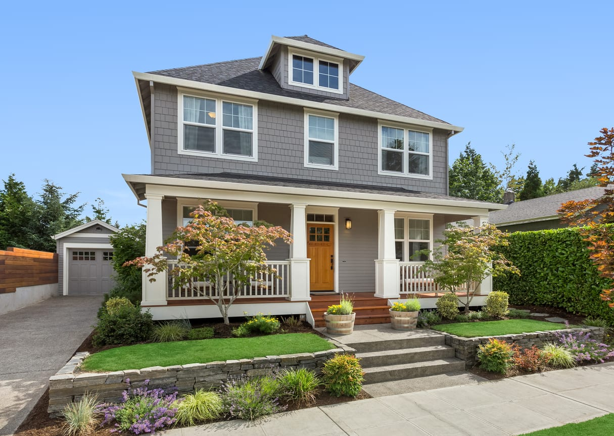 Beautiful craftsman home in Long Island NY exterior on bright sunny day with green grass and blue sky