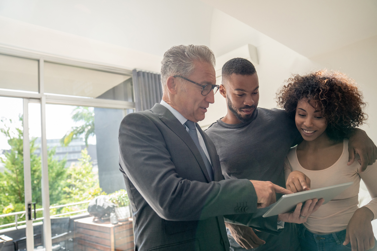 Real estate agent showing a property to an African American couple
